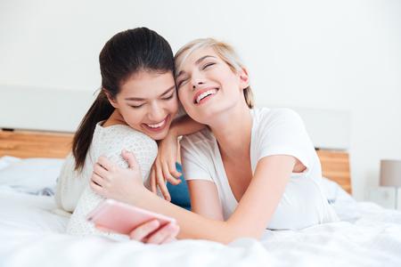 niñas sonriendo: Two happy girls hugging on the bed at home Foto de archivo