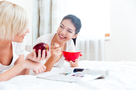 eating fruits: Two women lying on the bed with food and magazine at home Stock Photo