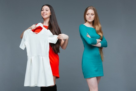 envious: Happy cheerful young woman and envious angry female on shopping over grey background