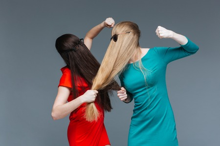 Two angry young women covered face with long hair and fighting over grey background