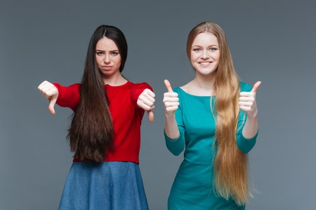 critique: Woman showing thumb down and her girlfriend showing thumb up over gray background