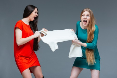 argues: Two pretty angry young women with long hair quarreling and fighting for white dress over grey background