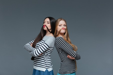 imitating: Two funny young women standing with arms crossed and making moustache with their hair over grey background