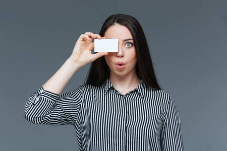 one eye: Funny woman covering eye with blank card over gray background