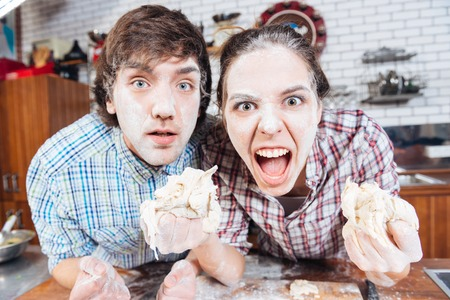 comical: Comical angry young couple with flour on their faces holding dough and shouting Stock Photo