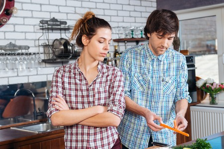 strict: Strict unhappy young woman cooking with her husband on the kitchen Stock Photo