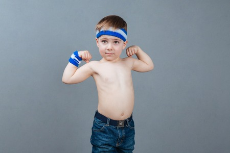 muscle boy: Portrait of shirtless little boy standing and showing biceps over grey background