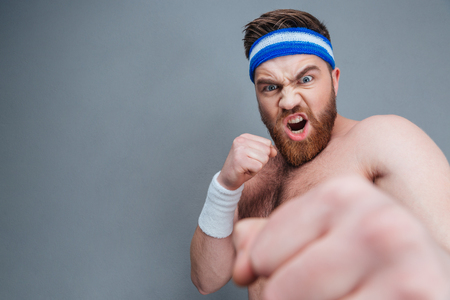 irritated: Mad irritated young sportsman shouting and punching at camera with his fist over grey background Stock Photo