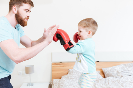 imitating: Cute little son in boxing gloves playing with his father at home