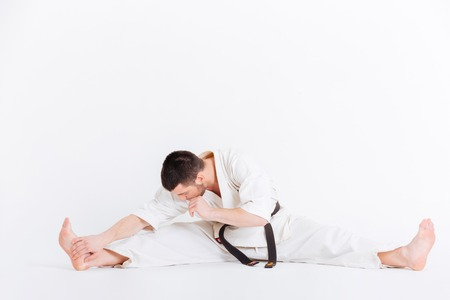limbering: Man in kimono limbering up isolated on a white background Stock Photo