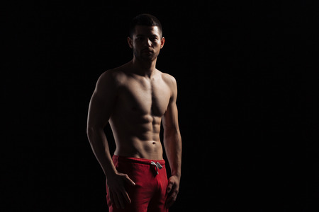 vexation: Silhouette of a muscular man standing over dark background Stock Photo
