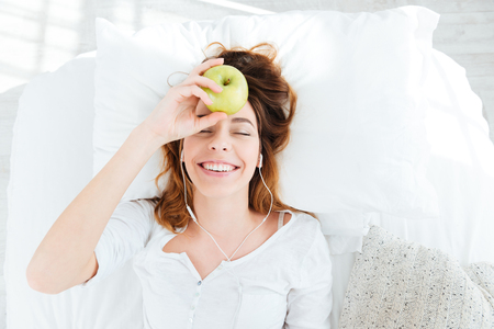 young adult woman: Happy woman with earphones holding apple on the bed at home