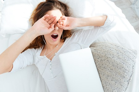 Young woman waking up and rubbing her eyes at home
