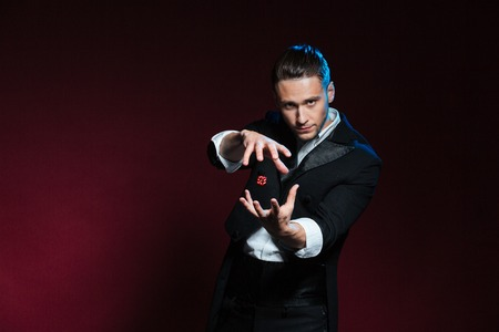 conjuring: Concentrated young man magician conjuring tricks with red dice  over dark background