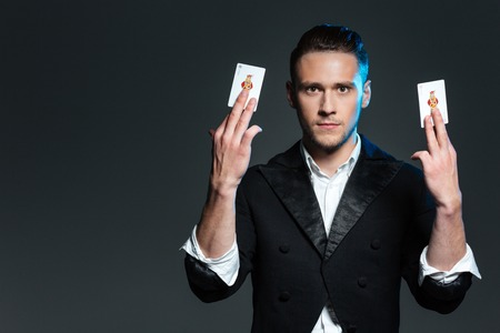 abracadabra: Attractive young man magician showing two jocker cards over grey background Stock Photo