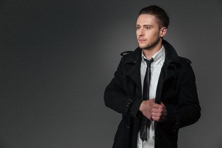 looking away from camera: Serious young businessman in black coat, white shirt and tie standing  over grey background