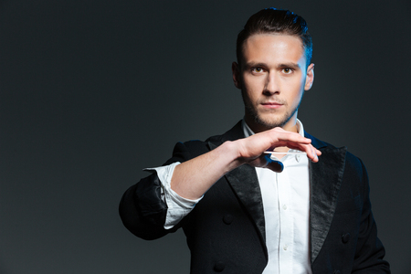 conjuring: Handsome young man magician showing tricks with playing cards over grey background Stock Photo