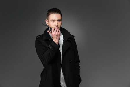 walkie talkie: Serious young man in black coat talking in walkie talkie over grey background Stock Photo