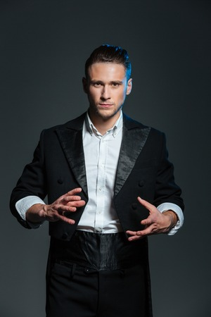 conjuring: Concentrated young man magician in black tail coat conjuring tricks over grey background