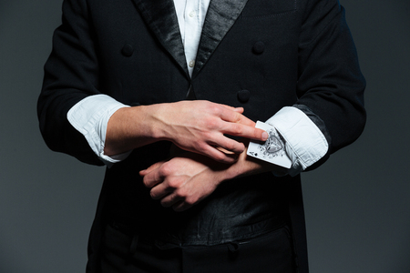 sleeve: Closeup of man magician in balck tail coat with ace in his sleeve over grey background