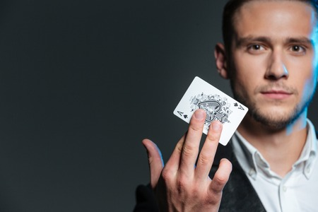Portrait of handsome young magician holding ace card over grey background