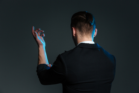 conjuring: Back view of young man magician standing with raised hand over grey background