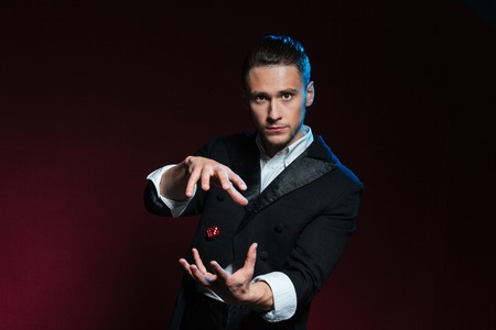 man flying: Confident young man magician showing tricks using one flying dice over dark background