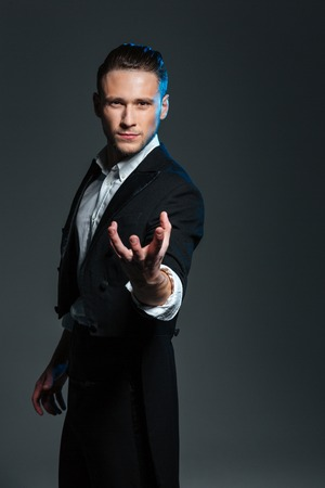 conjuring: Attractive mysterious young magician holding something on palm over grey background Stock Photo