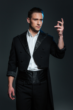 conjuring: Serious young man magician in black tail coat standing with raised hand and showing tricks over grey background