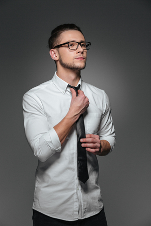 looking away from camera: Serious young businessman in glasses, white shirt and tie over grey background Stock Photo