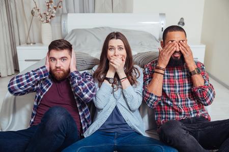Tres jóvenes amigos sentados en ver que el mal, no escuchar el mal, no hablar mal posa en casa Foto de archivo