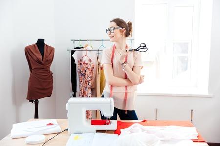 Vrolijke aantrekkelijke jonge vrouw naaister met een schaar staan en smilig in design studio