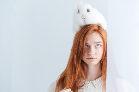 cabeza de mujer: Retrato de una hermosa mujer pelirroja posando con conejo en la cabeza aislado en un fondo blanco