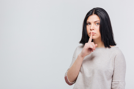 Portrait of young beautiful woman keeping finger on her lips and asking to keep quiet