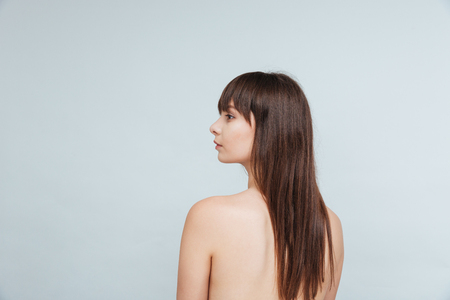 jeune fille adolescente nue: Rear view portrait of a naked woman looking away isolated on a white background Banque d'images
