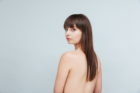 Portrait of a young naked woman looking back at camera isolated on a white background