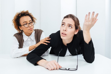 despaired: Pretty african american young businesswoman in glasses sitting and supporting her upset despaired colleague in office