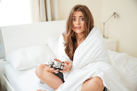 scared woman: Scared woman holding alarm clock on the bed at home and looking at camera Stock Photo