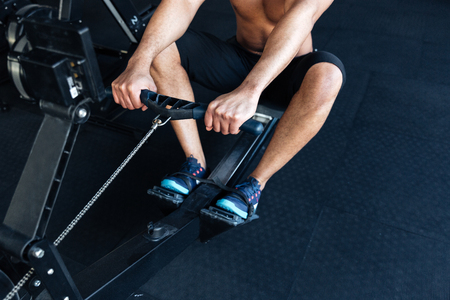 Cropped image of a muscular fitness man using rowing machine in the gym