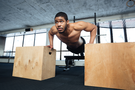 musculine: Healthy fitness man doing push-ups in the gym using sports equipment