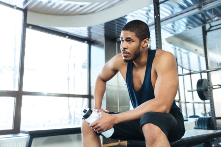 body built: Afro american fitness man resting on the bench in the gym Stock Photo