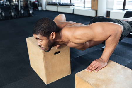 musculine: Muscular fitness man doing push-ups in the gym using sports equipment