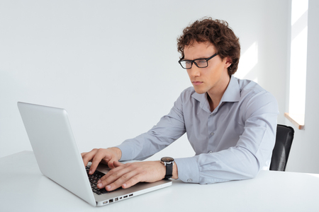 concentrated: Concentrated businessman using laptop computer in office Stock Photo