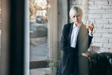 short haired: Short haired blonde girl holding a glass of whiskey in a bar