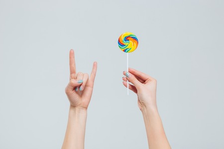 female devil: Female hands holding lollipop and showing devil sign isolated on a white background