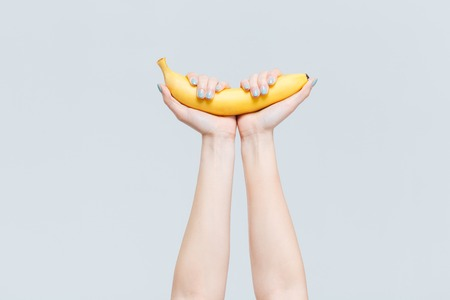 Female hands holding banana isolated on a white background Stock Photo