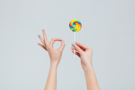licking finger: Coseup portrait of female hands holding lollipop and showing ok sign with fingers isolated on a white background Stock Photo