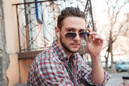 Man in sunglasses and earphones looking at camera outdoors Stock Photo