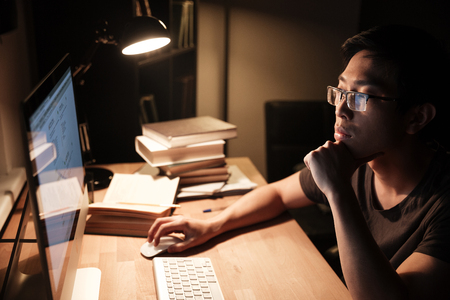Pensive asian young man in glasses working with computer and thinking in the evening at home
