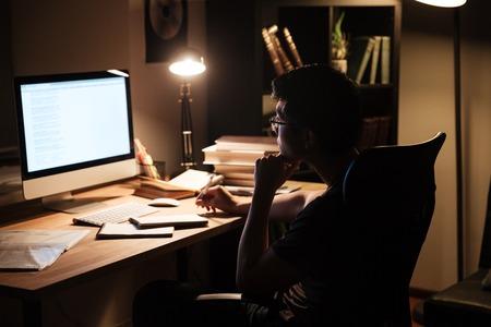usando computadora: Asia joven pensativo sentado y estudiando el uso de la computadora en una habitación oscura en el hogar